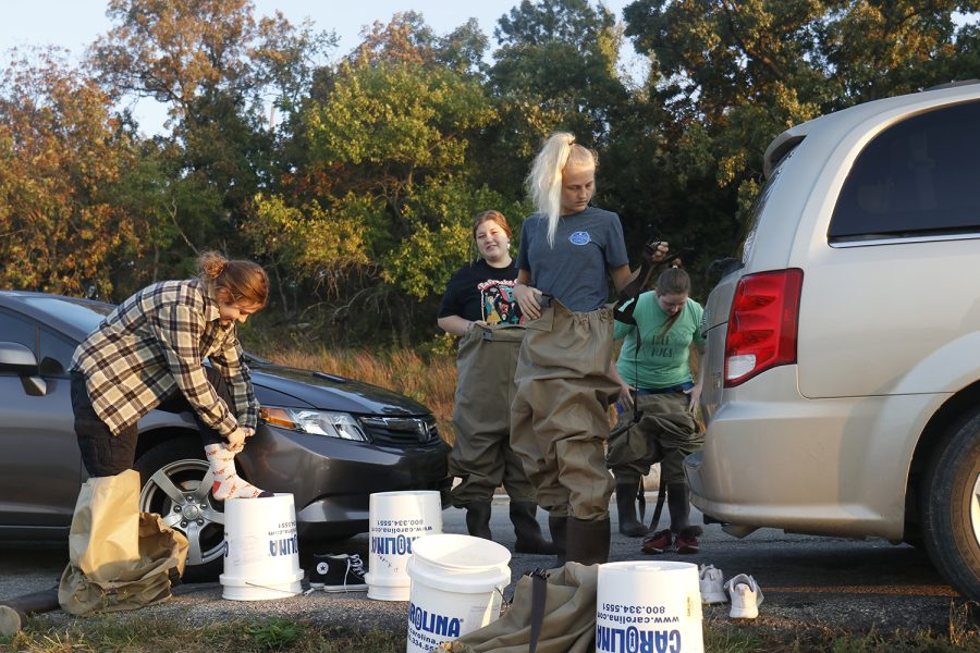 On the side of the road, Environmental Resources and Wildlife Science students put on waders before going into the water to collect plants.